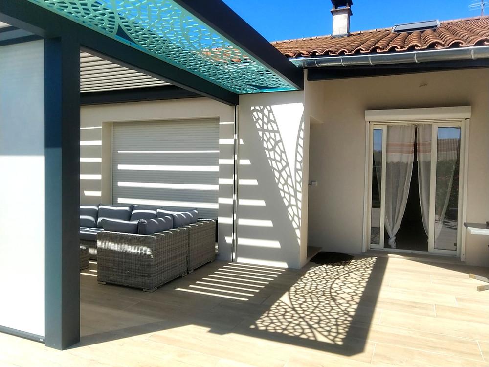 Pergola bioclimatique gris anthracite sur-mesure Sol Design Solembra avec lames orientables et accessoires haut-de-gamme claustra décoratifs bleu vertical et jeux d'ombres et de lumières sur la façade et le sol avec store zip screen vue de dessous