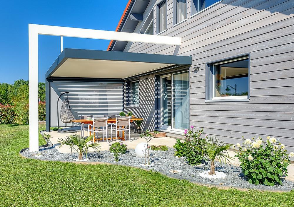 Pergola bioclimatique design et sur-mesure avec arche suspendue et store fabricant français Solembra sur terrasse propre et jardin paysager entretenu
