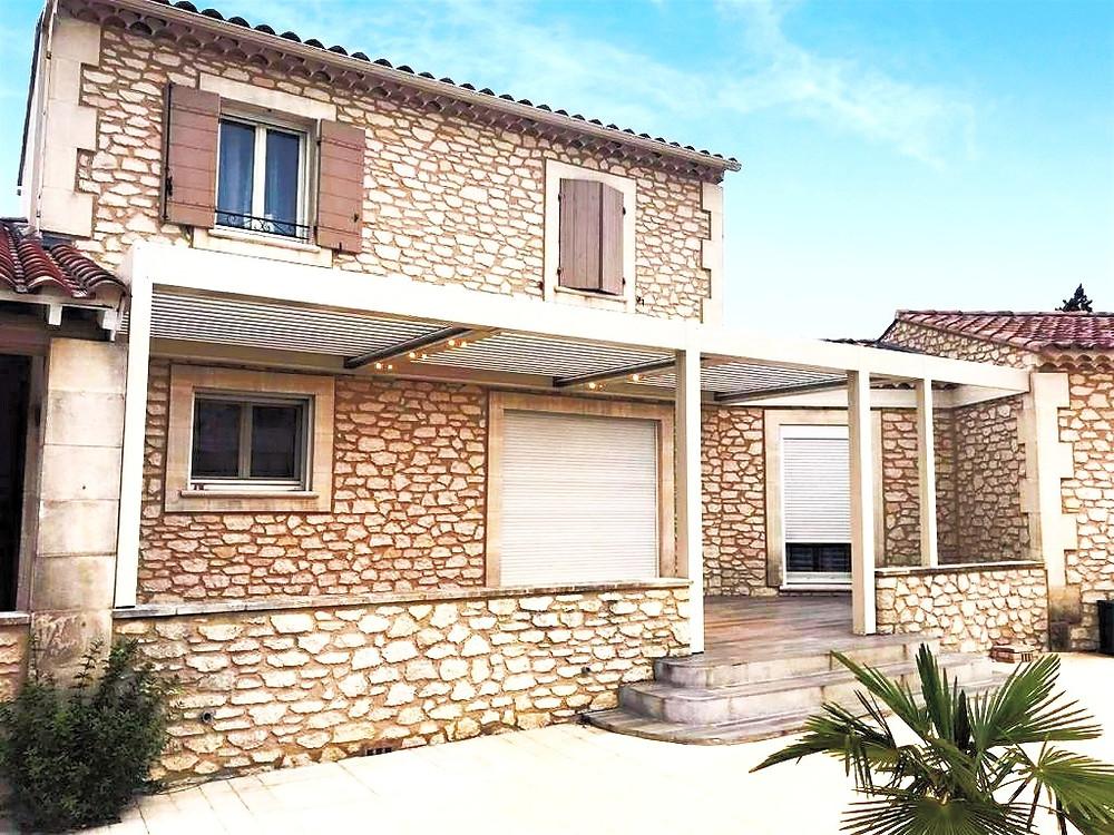 Photo de la pergola bioclimatique sur-mesure Sol Design Solembra avec spots led éclairés et évacuation d'eau déportée dans le buisson avant la pose des vitrages sur une maison en pierre rénovée par nos clients à Arles, Bouches-du-Rhône, dans le Sud de la France