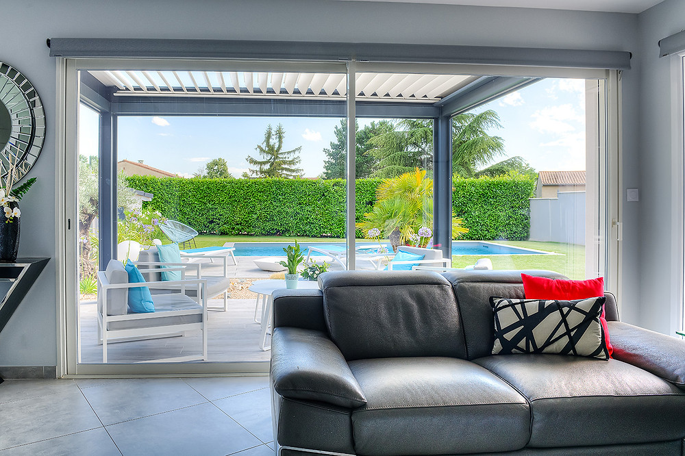 Pergola bioclimatique Sol Izzy Solembra vue de l'intérieur de la maison qui laisse entrer la lumière naturelle dans la maison