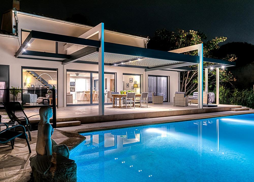 Pergola bioclimatique Sol Design Solembra gris anthracite aux lignes architecturales et élégantes avec 2 arches blanches suppression de poteau par haubanage et éclairages LED