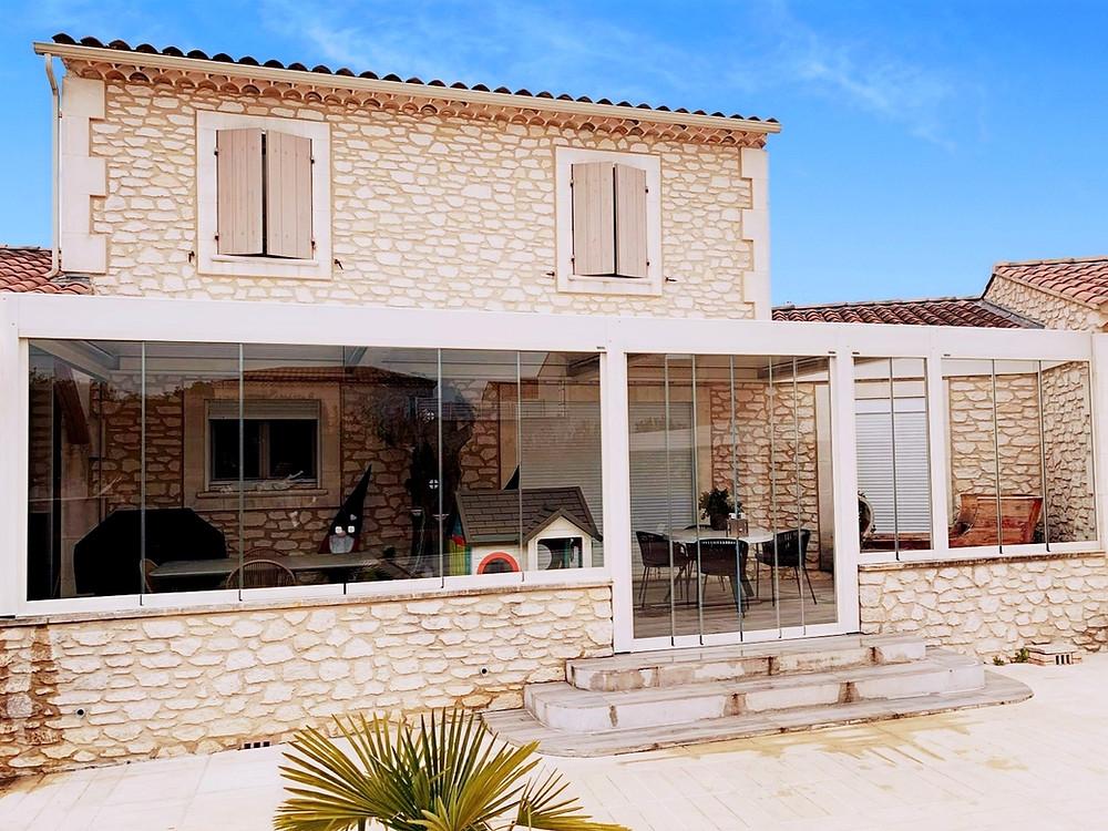 Photo de la pergola bioclimatique sur-mesure avec vitrage Sol Design Solembra sur maison en pierre rénovée de nos clients à Arles, Bouches-du-Rhône, dans le Sud de la France, comme nouvelle pièce de vie en toutes saisons - vue de face