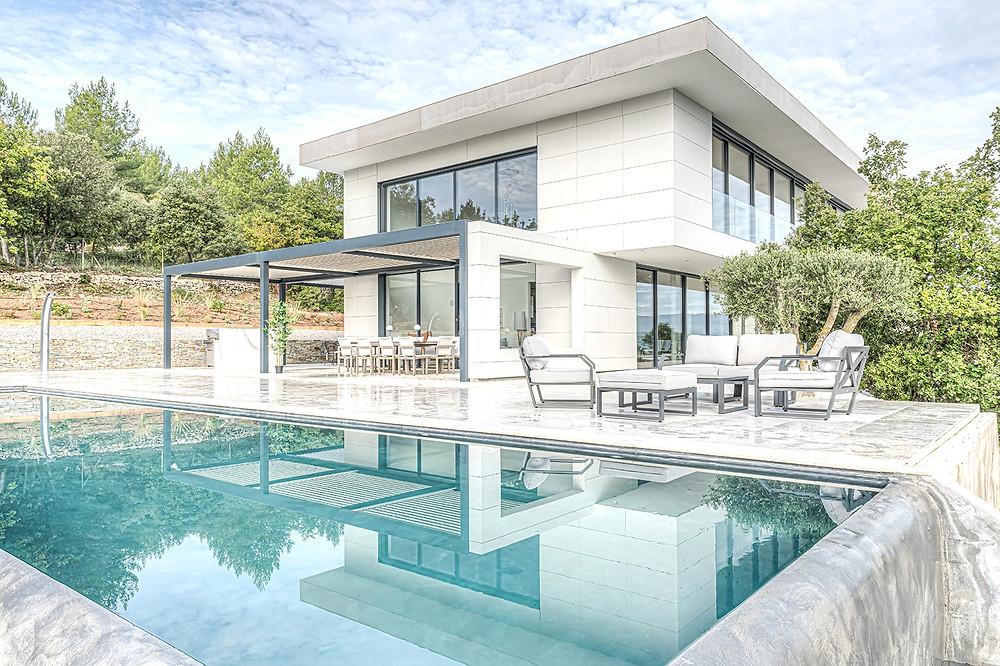 Pergola bioclimatique Sol Design Solembra avec portée XXL poteau décalé pour une ouverture de vue optimale depuis la baie vitrée et intégration sur-mesure à l'architecture existante de cette maison contemporaine vue de la piscine