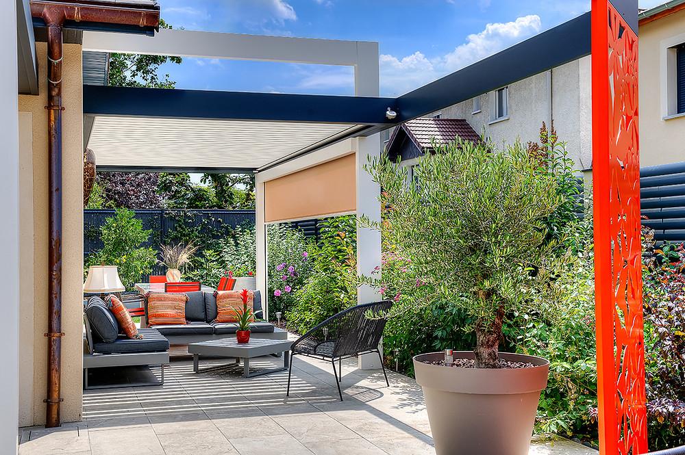 Pergola bioclimatique Sol Design Solembra gris anthracite et blanche avec arche, claustra décoratif, store zip screen et détecteur de pluie