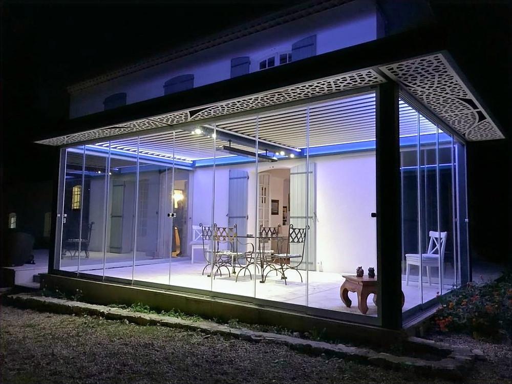 Pergola bioclimatique à lames orientables Sol Design Solembra avec vitrages et claustra décoratif