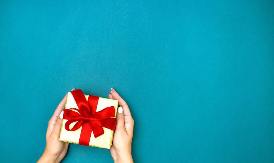 female-hands-holding-gift-blue-backgroun
