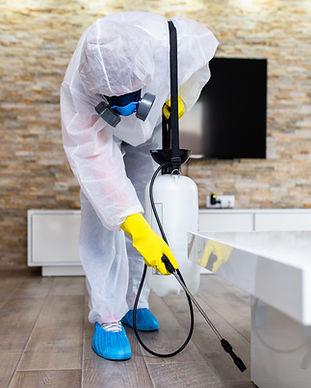 Exterminator in work wear spraying pesti