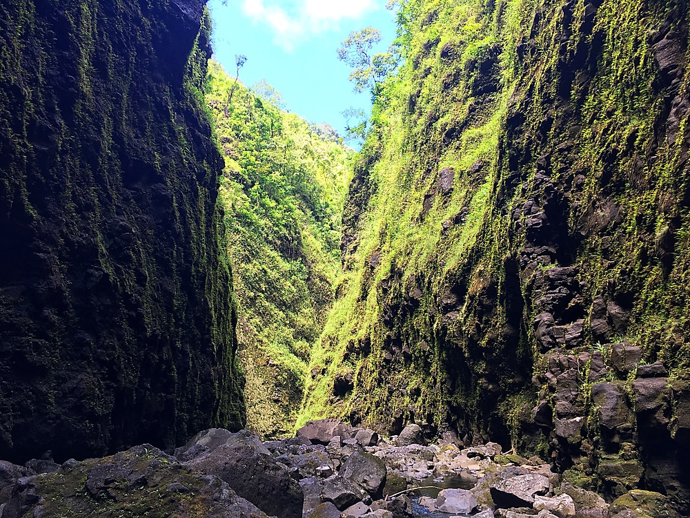 Local style hike through a rocky stream to a giant waterfall