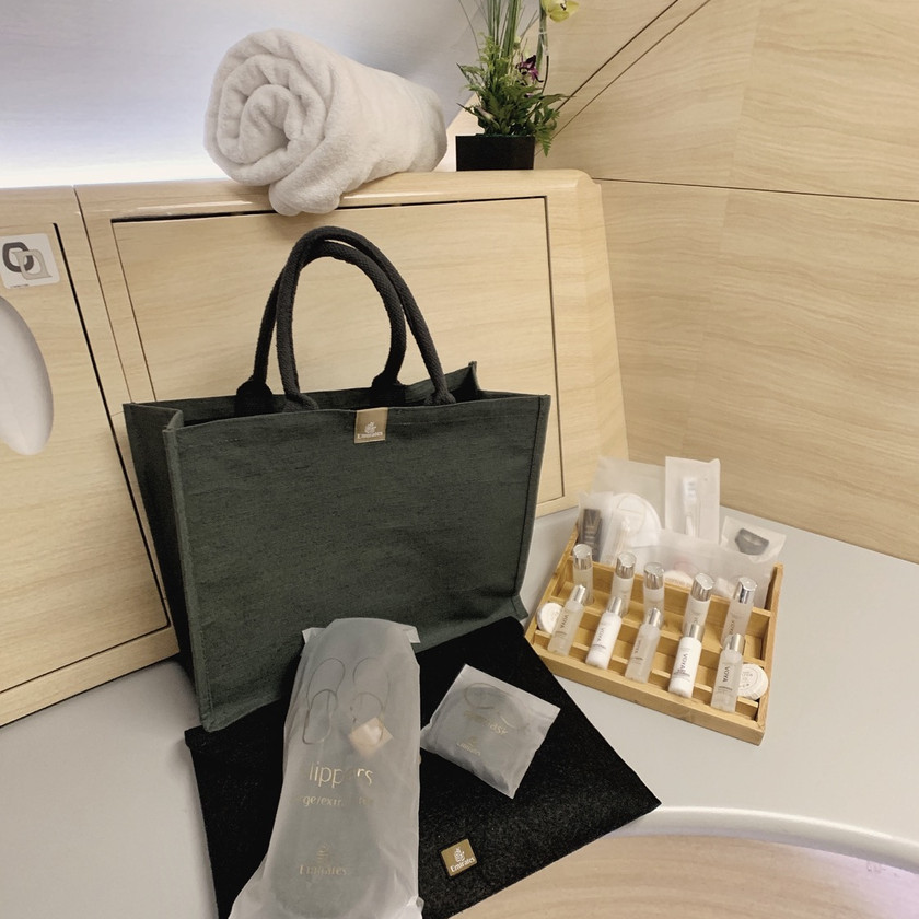 The Emirates First Class A380 Pajama Set, Beach Tote, and shower gels neatly placed and organized by the Shower Attendant.