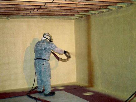 Man installing insulation in basement