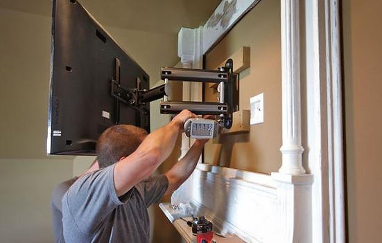 handyman working on mounting and install
