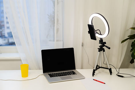 laptop, lamp and tripod on the table for online interview.jpg