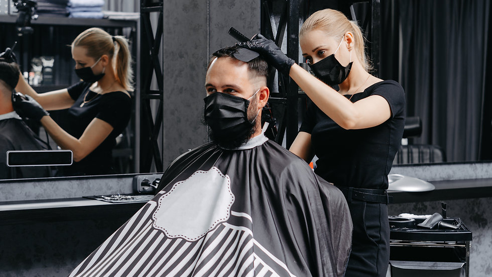 Woman barber cutting hair to a bearded m