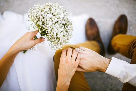 Bride and groom holding hands with white wildflower bouquet