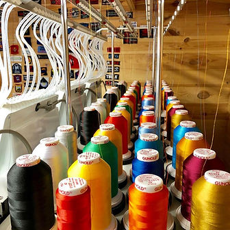 Photo of the top/back of an embroidery machine with various coloured threads