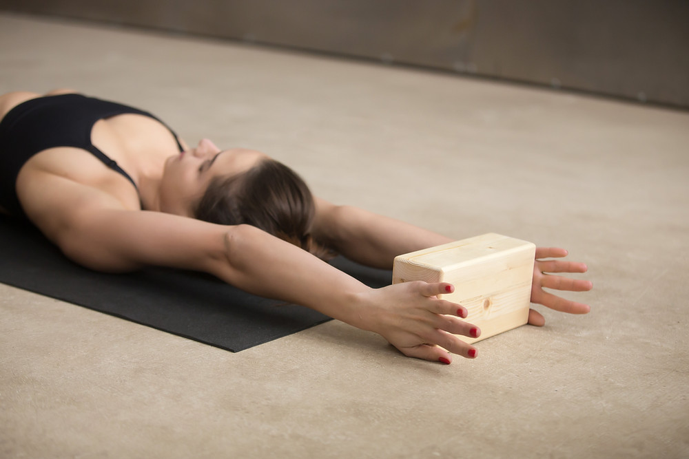 Supported yoga stretch with block.