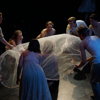 The ensemble creates the statue scene.