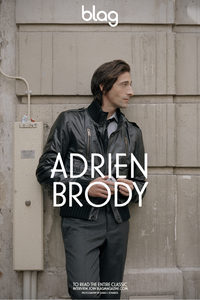 A photo of actor Adrien Brody on the streets of Paris, against a traditional stone wall, wearing a black leather jacket, suit trousers, shirt and tie