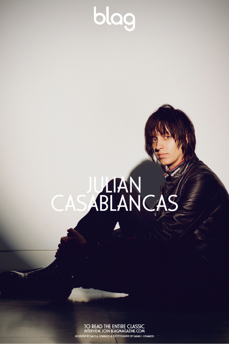 Julian Casablancas portrait for BLAG magazine. The singer is dressed in black, sitting on the floor and lit by a spotlight.