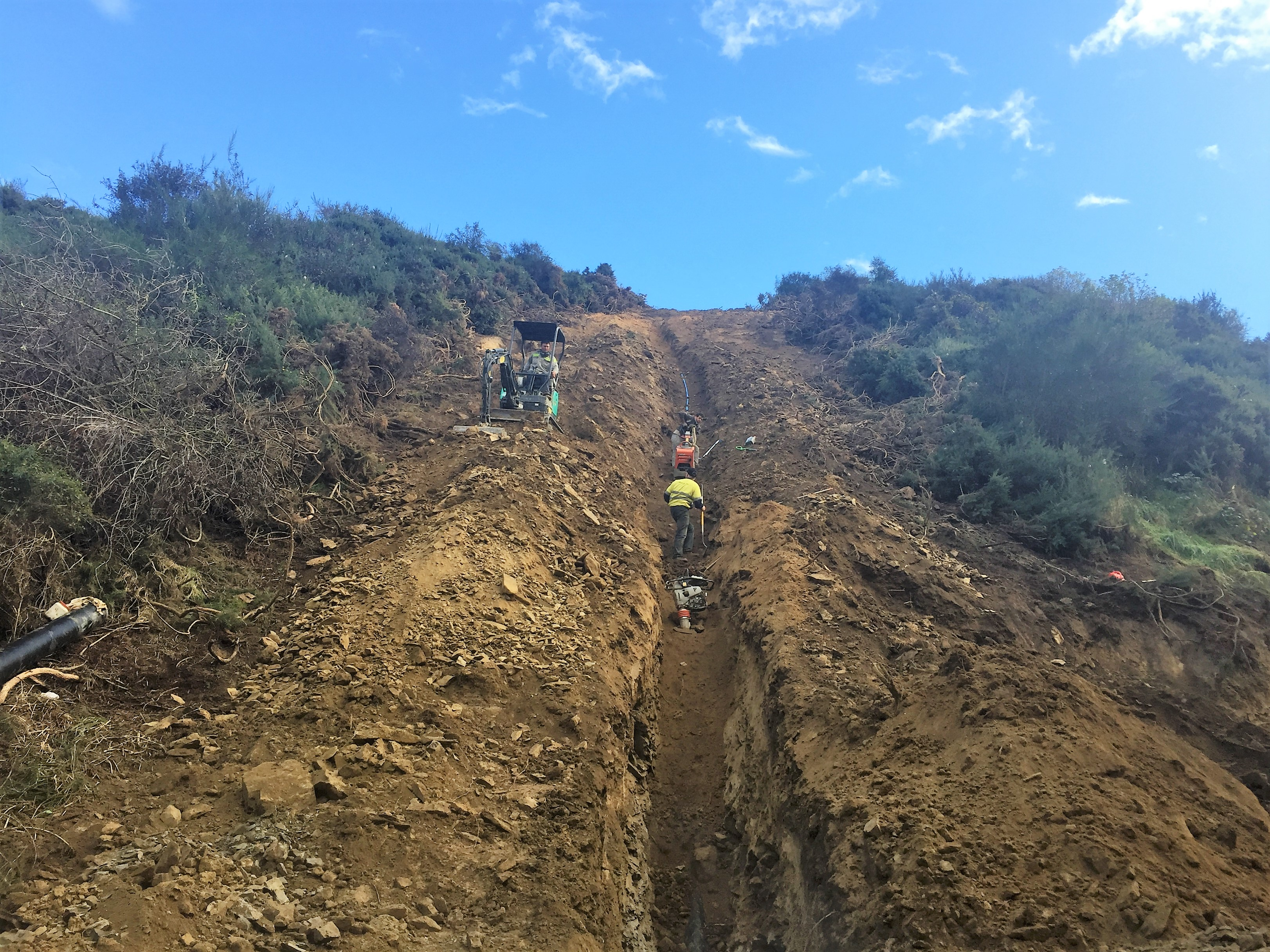 Backfilling and compacting on steep hill face