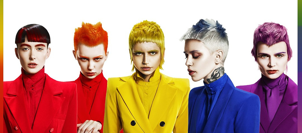 Five people with different coloured hair and clothes stand in a row.