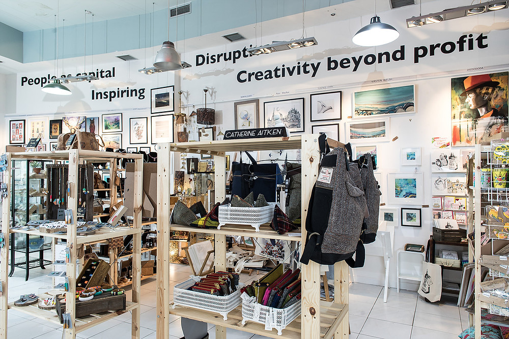 A photo of The Scottish Design Exchange's flagship store at Ocean Terminal. The foreground shows two shelves holding crafts including purses and earrings. The background shows a wall of paintings and prints by various artists.