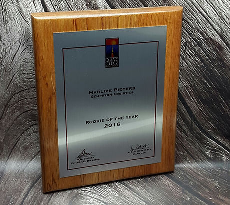 Custom wooden plaque with brushed silver plate for awards or building dedications.