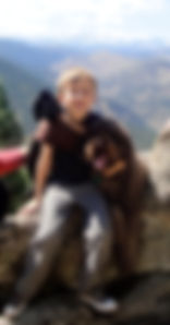 Young boy hiking with an Australian Labradoodle dog outoors in Colorado
