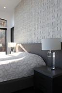 modern lake house. master bedroom. stone tile wall treatment
