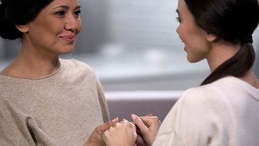 Caring mother holding hands of beloved y