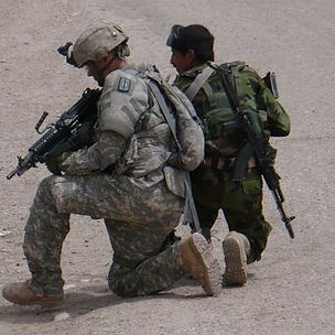 US Army kneeling with weapon with a soldier from the Iraqi Army.
