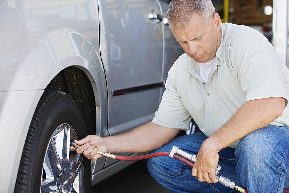 Man at auto shop checking tire pressure