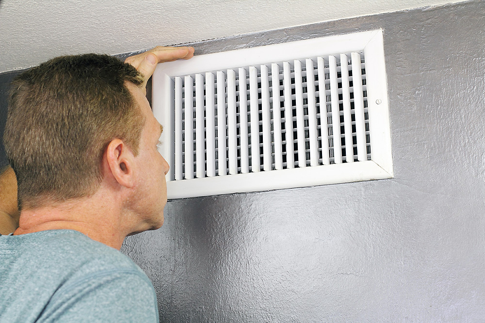 Man inspecting air vent in green building