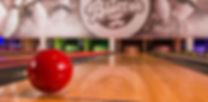 close up image of a bowling ball with the background lanes fading into the depth of field - somebody forgot to remove the napkin from under the ball to keep it from rolling away and you can kind of see it if you look closely.