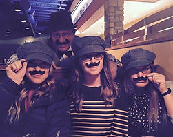 image of one man and 3 women wearing fake mustaches