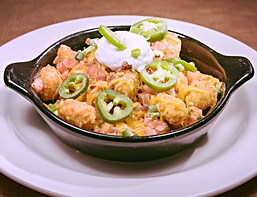 image of loaded tater tot mountain in a black bowl