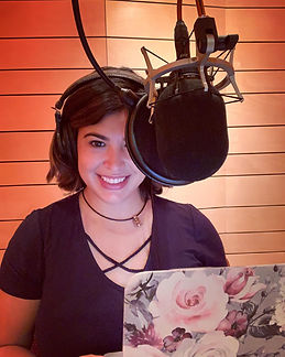 Maria Liatis in front of a microphone during an audiobook narration session.