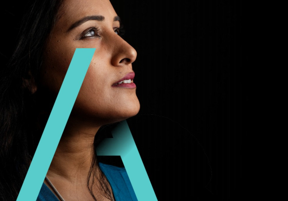 A close up image of a woman looking into the distance with a teal A superimposed on her profile.