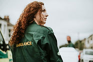 A woman with curly hair looking into the distance wearing a green jacket.