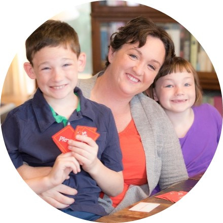 Congresswoman Katie Porter at home with two of her children, a young boy and girl, smiling while playing cards.