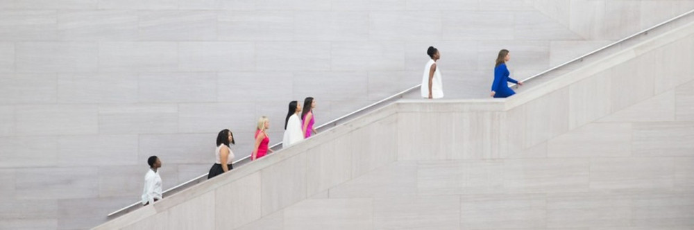Seven women ascending a flight of stairs in professional clothing.