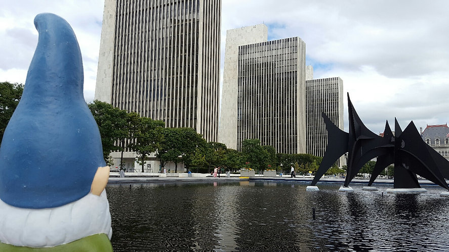 The Capital District Tourism Gnome looking over the Empire State Plaza