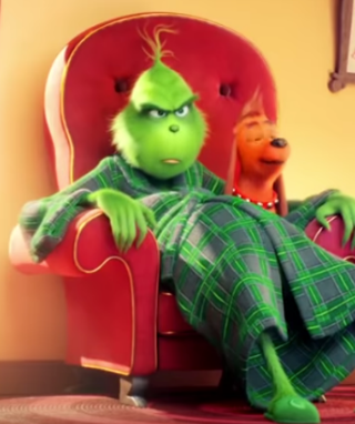 The Grinch sits on the sofa with his dog, Max