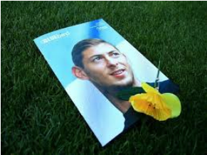 A printed photo of Emiliano Sala on grass, next to a yellow daffodil flower.