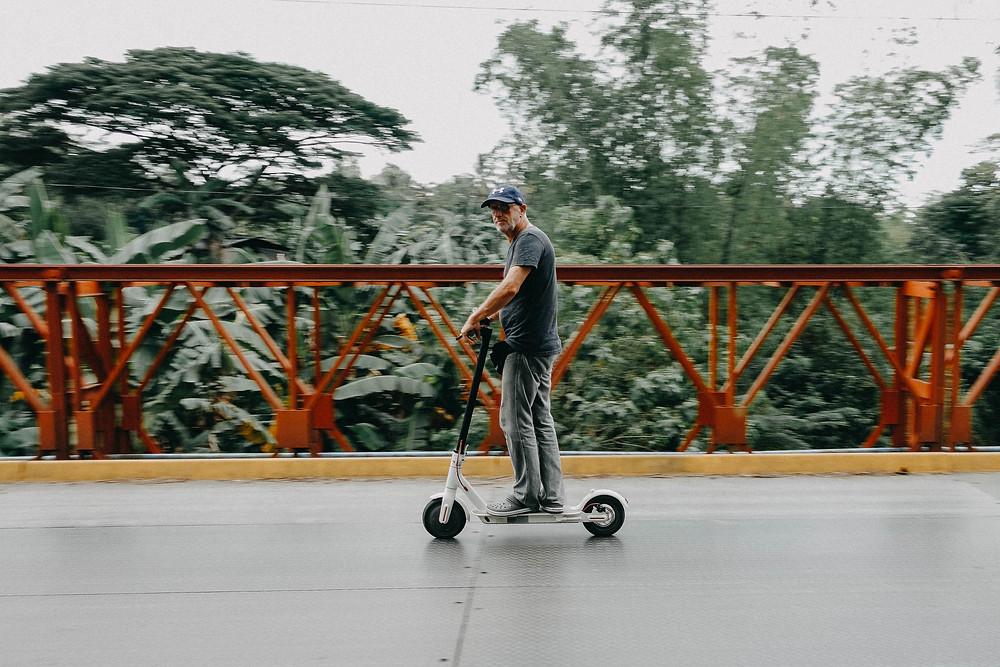 """A man riding a """"Bird"""" scooter"""
