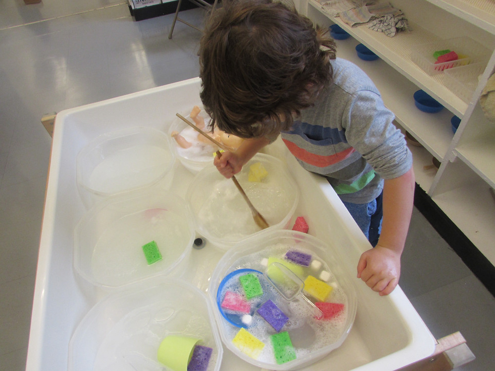 Oscar Edgerton playing at the water table