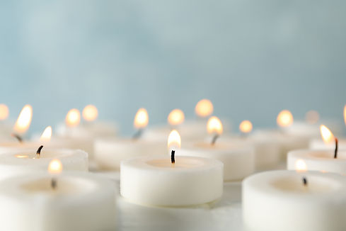 Group of burning candles against blue ba