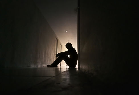 Silhouette of depressed man sitting on w