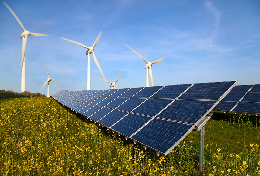 Stock image of solar panels with windmills in the background