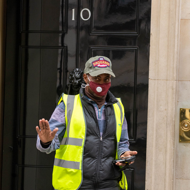 A masked delivery driver at the door of 10 Downing Street